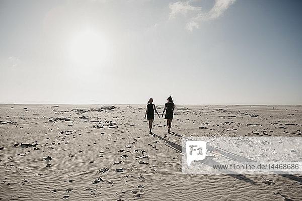 Südafrika  Westkap  Strand von Noordhoek  Rückenansicht zweier junger Frauen beim Strandspaziergang