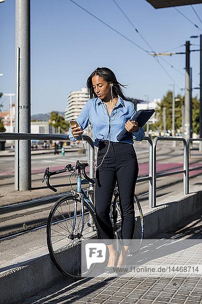 Geschäftsfrau mit Smartphone  Laptop-Tasche