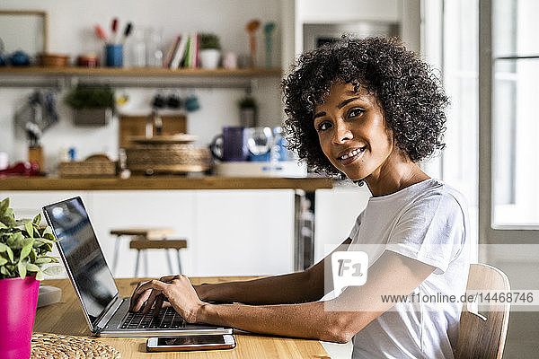 Portrait of smiling woman using laptop at table at home