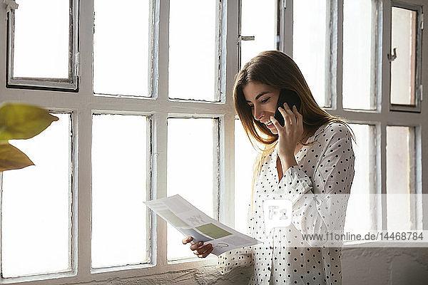 Glückliche junge Frau am Handy  die am Fenster auf ein Dokument schaut