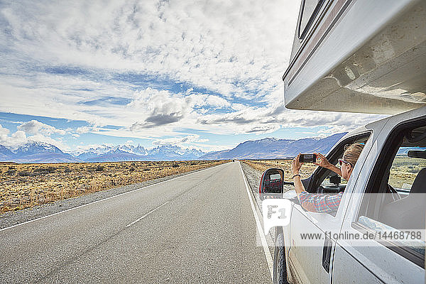 Argentina  Patagonia  El Chalten  woman taking cell phone picture in camper on road towards Fitz Roy