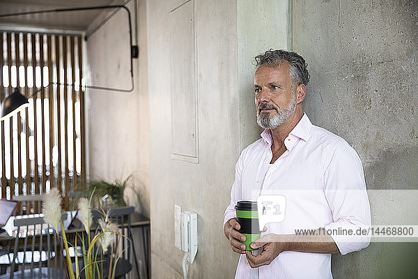 Lächelnder Geschäftsmann hält Kaffeetasse an Betonwand in einem Loft