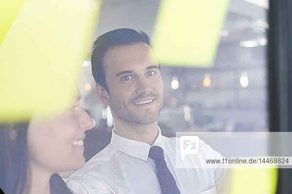 Businessman with colleague brainstorming with post-its on window front