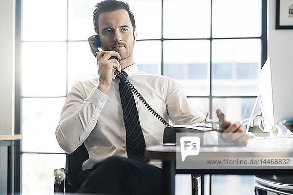 Geschäftsmann im Büro benutzt altes Retro-Telefon