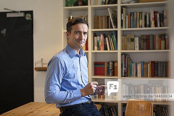 Porträt eines selbstbewussten Geschäftsmannes mit Tablett am Tisch lehnend mit Bücherregal im Hintergrund