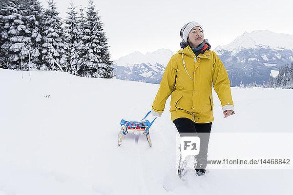 Österreich  Tirol  Thurn  reife Frau beim Schlittenziehen in schneebedeckter Landschaft