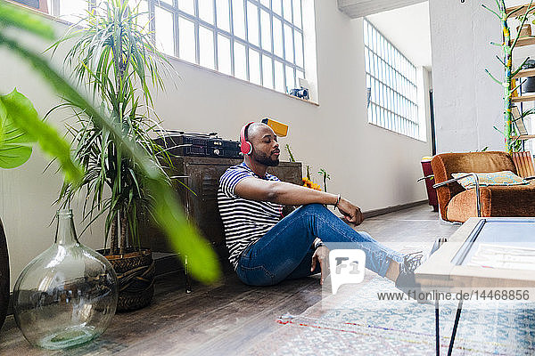 Young man with headphones sitting on floor in a loft