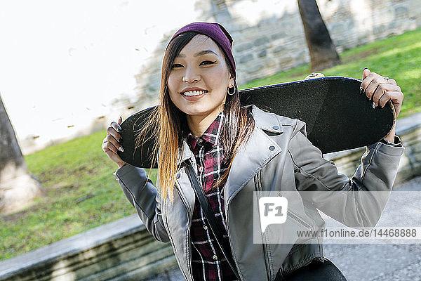 Porträt einer lächelnden jungen Frau mit Skateboard auf den Schultern