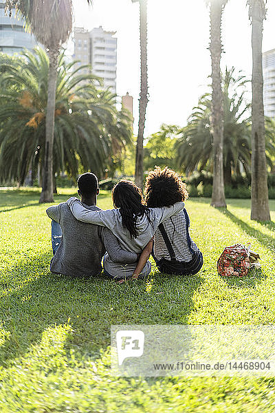 Drei Freunde sitzen in einem Park und beobachten den Sonnenuntergang