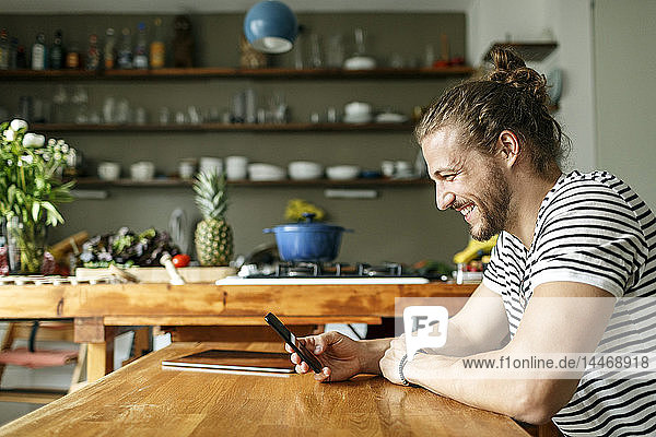 Young man with a bun sitting at home  using smartphone