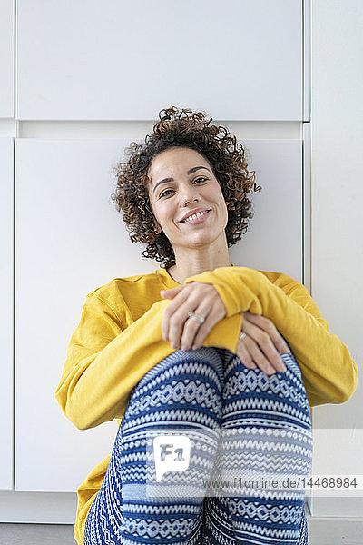 Porträt einer lächelnden Frau  die zu Hause auf dem Boden sitzt