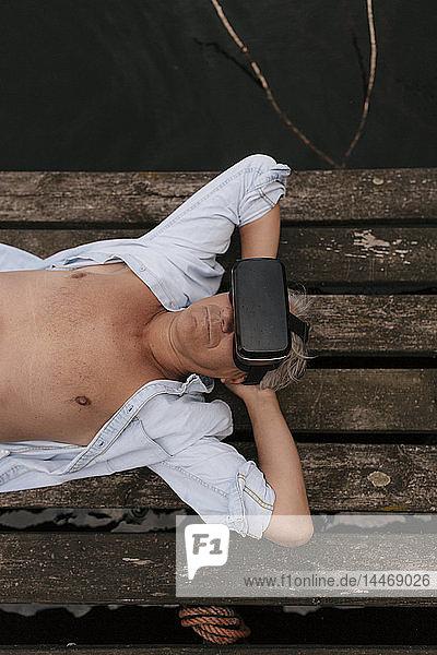 Älterer Mann  der mit einer VR-Brille auf einem Steg an einem See liegt