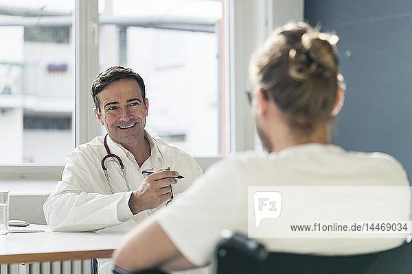 Lächelnder Arzt im Gespräch mit Patient im Rollstuhl in der medizinischen Praxis