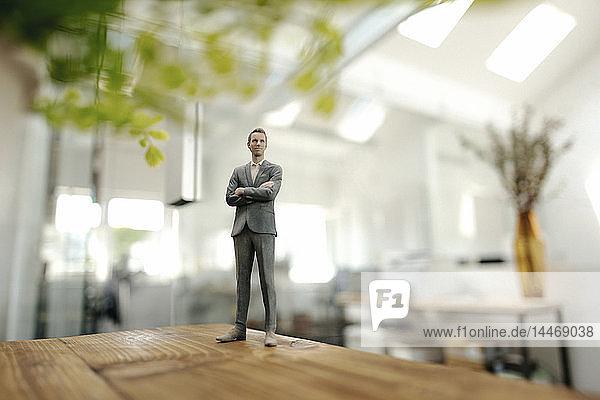 Businessman figurine standing on desk in modern office