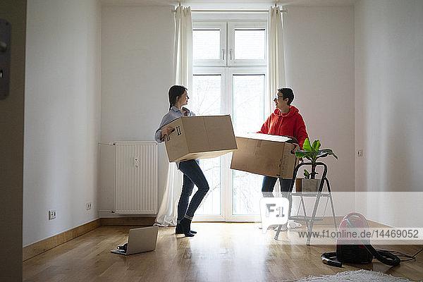 Junge Frauen ziehen in ihr neues Zuhause ein und tragen Kartons