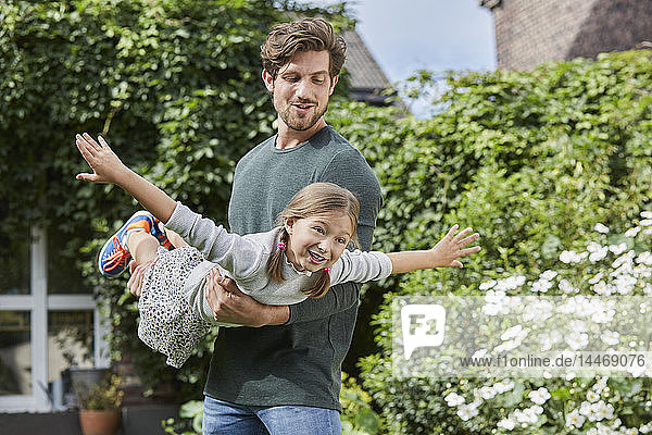 Happy father playing with daughter in garden of their home