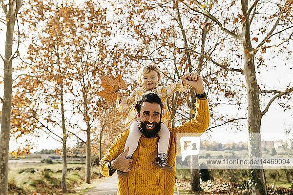 Vater trägt seine kleine Tochter an einem Morgen im Herbst im Park auf den Schultern