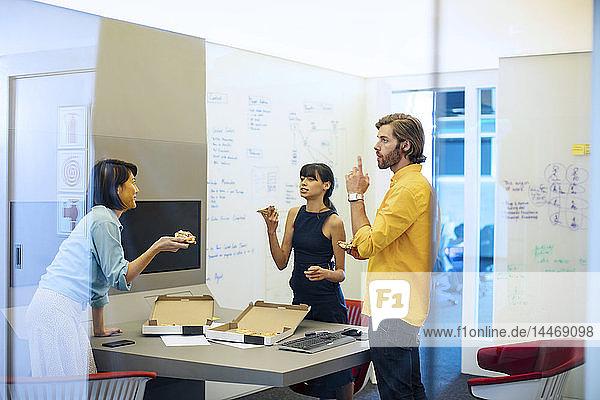 Geschäftsleute in futuristischem Büro bei einer Besprechung  beim Pizzaessen
