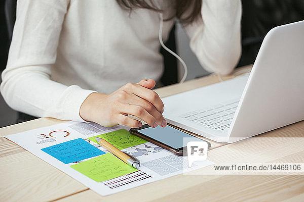 Nahaufnahme einer Frau mit Dokument  Handy und Laptop am Schreibtisch im Büro