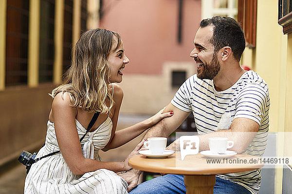 Spanien  Andalusien  Malaga  glückliches Paar beim Kaffee trinken in einer Gasse