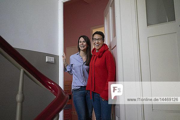 Zwei Freundinnen zu Hause stehen im Türkasten  mit den Armen um den Hals
