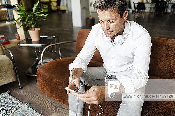 Mature man with cell phone and headphones sitting on couch in a loft
