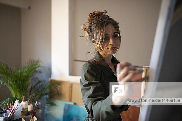 Junge Frau malt in ihrem Atelier
