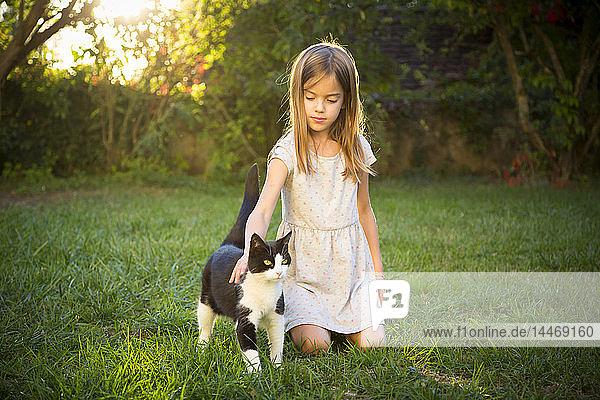 Portrait of little girl stroking cat in the garden
