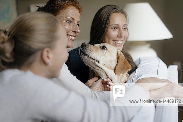 Glückliche Mutter mit zwei Mädchen im Teenager-Alter und Hund auf der Couch zu Hause