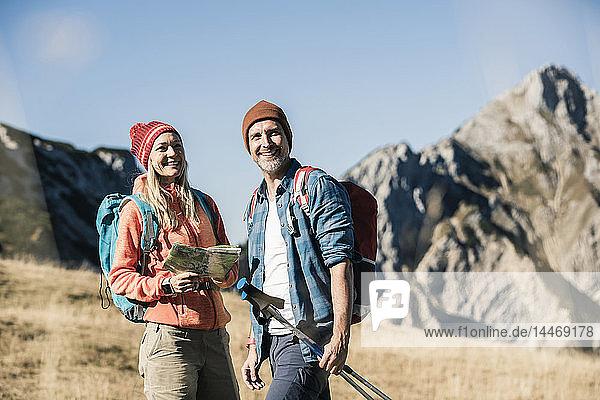 Österreich  Tirol  glückliches Paar mit Karte auf einer Wanderung in den Bergen