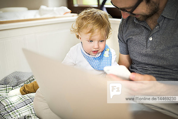 Father at home with his little son using laptop and cell phone