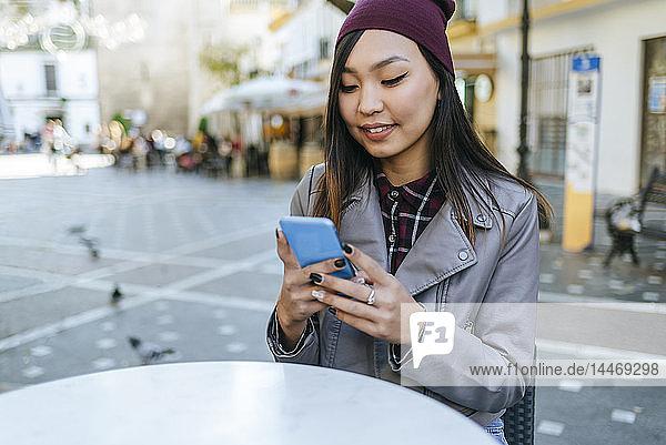 Porträt einer jungen Frau mit Smartphone im Straßencafé