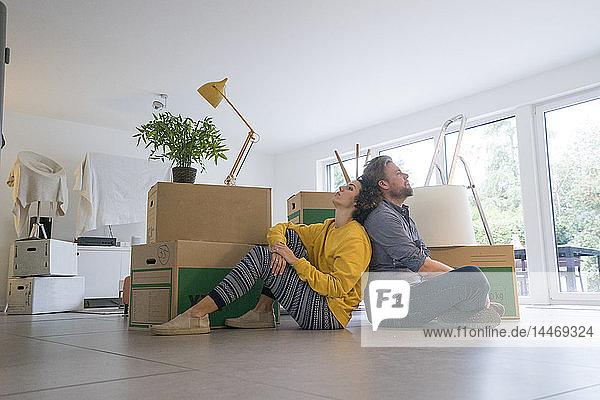 Im Wohnzimmer sitzendes Ehepaar mit Pappkartons