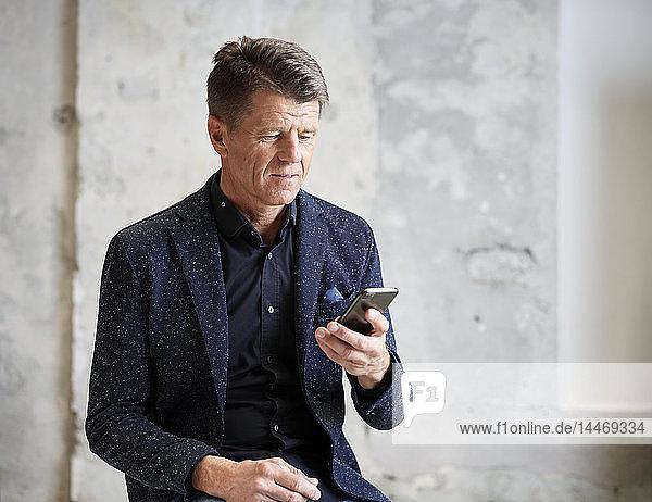 Geschäftsmann schaut auf Handy