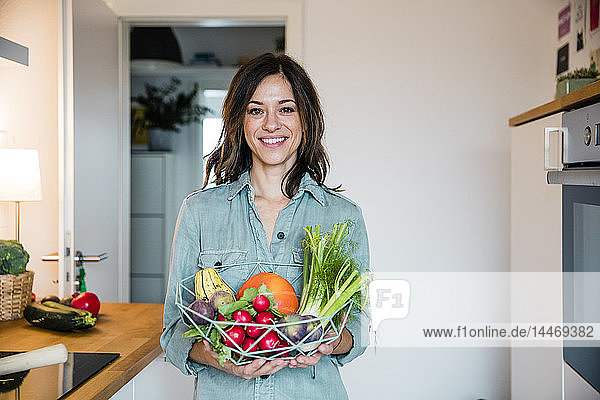 Woman standing in kitchen  holding basket full of fresh fruit and vegetables