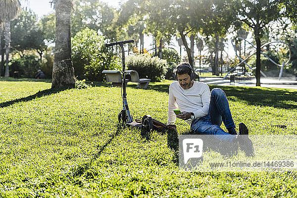 zufälliger Geschäftsmann  der auf einem Rasen in einem Park sitzt und ein Smartphone und Kopfhörer benutzt