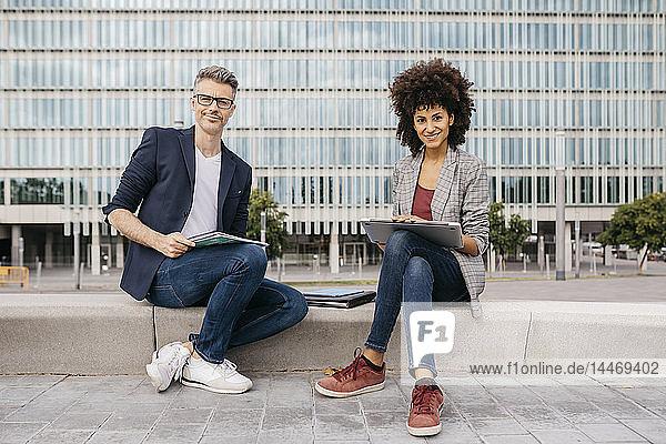 Porträt von zwei selbstbewussten Kollegen  die vor dem Bürogebäude zusammenarbeiten