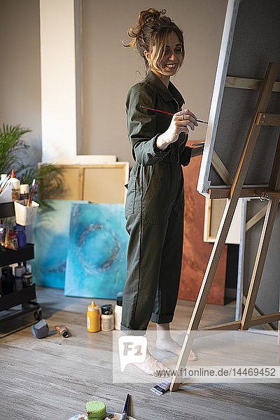 Young woman painting in her atelier
