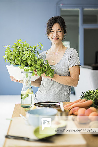 Woman standing in kitchen  holding pot of basil