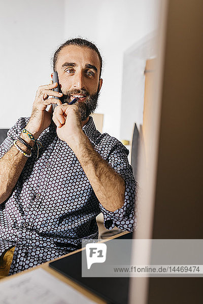 Young man at home working on the computer while talking on the phone