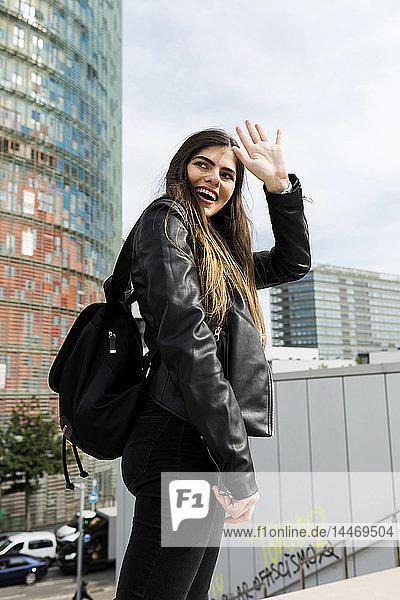 Spanien Barcelona  lächelnde junge Frau in der Stadt dreht sich um und grüßt jemanden