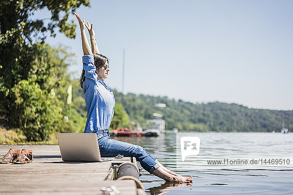 Woman with laptop sitting on a jetty at a lake  stretching
