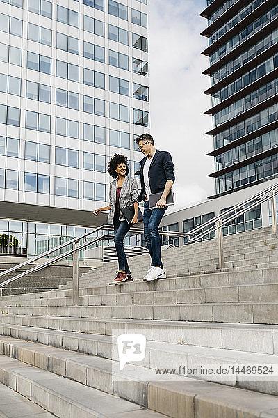 Zwei Kollegen gehen und sprechen auf einer Treppe vor einem Bürogebäude in der Stadt