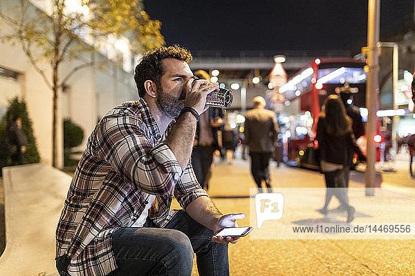 UK  London  Mann sitzt nachts auf einer Bank und trinkt aus einem Becher