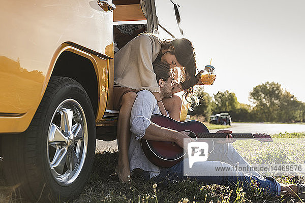 Affectionate couple on a road trip  taking a break  kissing  playing guitar