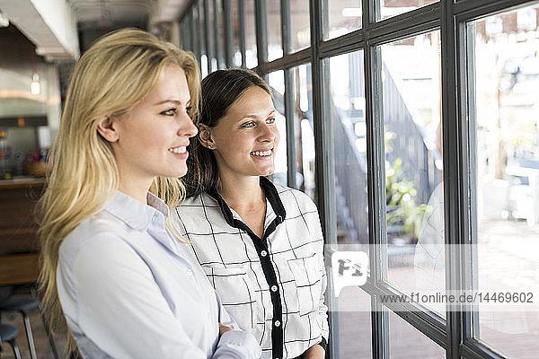 Zwei lächelnde Kolleginnen schauen aus dem Fenster