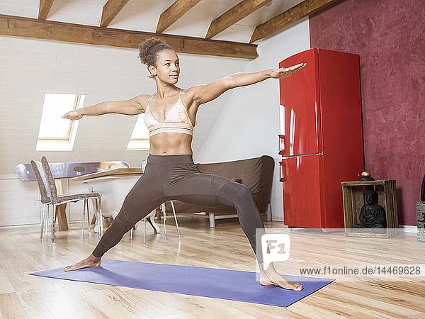 Junge Frau praktiziert Yoga auf dem Dachboden