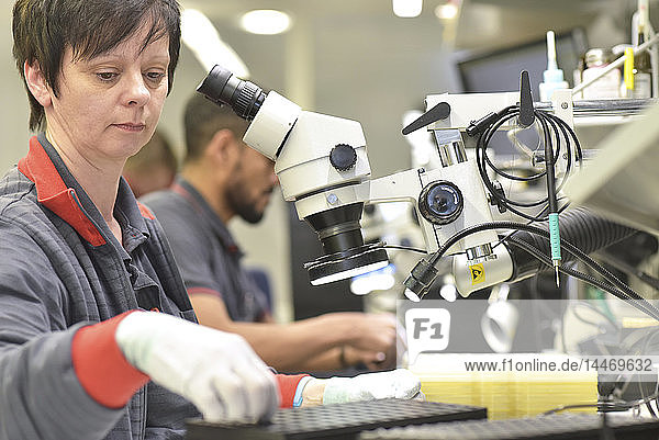 Frau  die an der Qualitätskontrolle bei der Herstellung von Leiterplatten für die Elektronikindustrie arbeitet