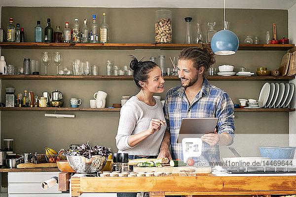 Junges Paar bereitet gemeinsam Spaghetti zu  mit Online-Rezept