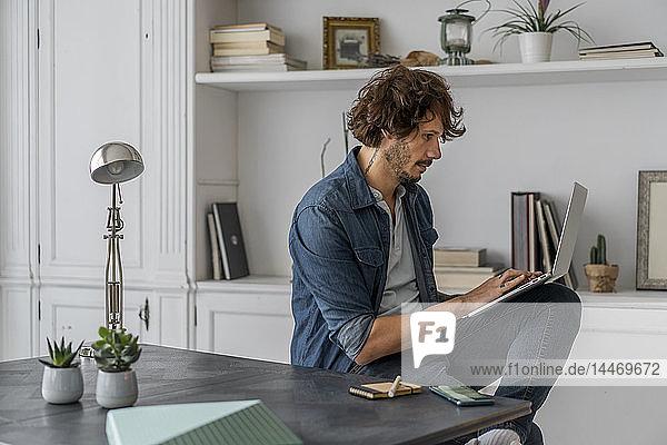 Mann  der im Coworking Space arbeitet und einen Laptop benutzt